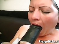 A horny slut has a huge toy inside of her cunt!