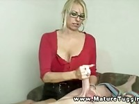 Blonde MILF with sexy glasses tugging a hard cock