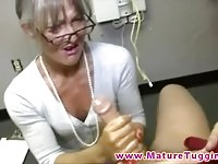 Hot MILF with glasses stroking a young cock like a pro
