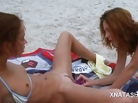 Two sexy teen lesbians toying their twats on the beach