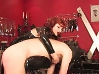 Latex mistress punishing dude