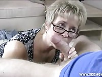 Horny mature with glasses sucking a young cock