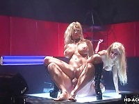 Two busty ladies in sex show sharing a dong