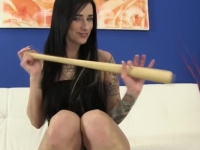 Tattoed raven haired babe playing with a basketball bat