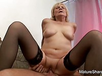 Blonde mature in stockings riding a young man's cock