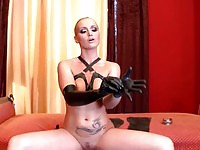 BDSM femdom putting on her leather outfit